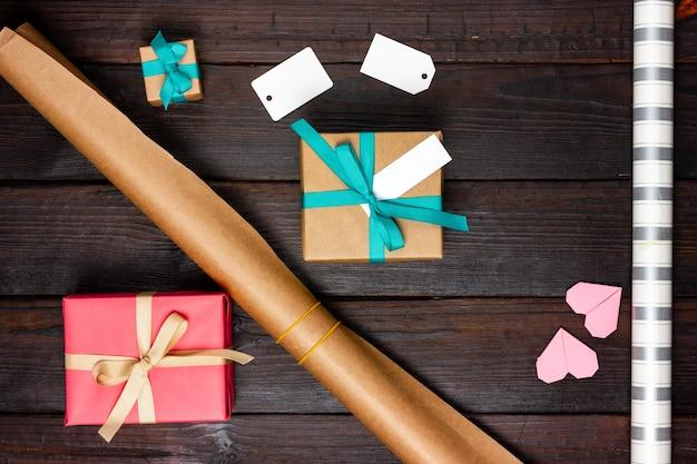 Papel de embrulho, presentes e etiquetas de papel em branco sobre uma mesa de madeira. Foto Premium