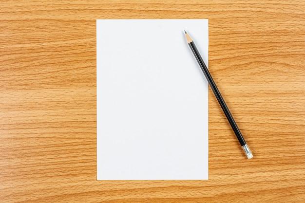 Papel de nota em branco e um lápis na mesa de madeira. - espaço em branco para texto publicitário. Foto Premium