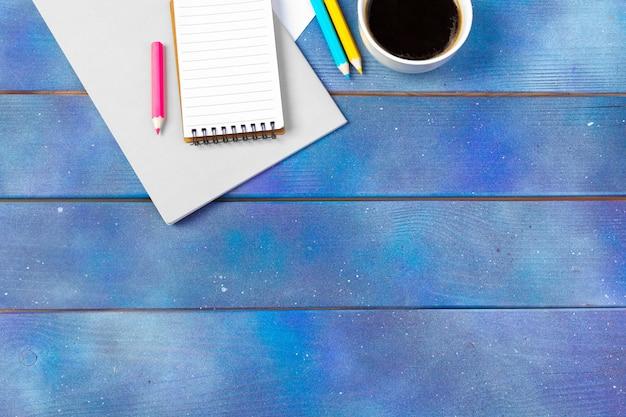 Papel de nota vazio com xícara de café sobre fundo azul de madeira. escritório, escritor ou conceito de estudo Foto Premium