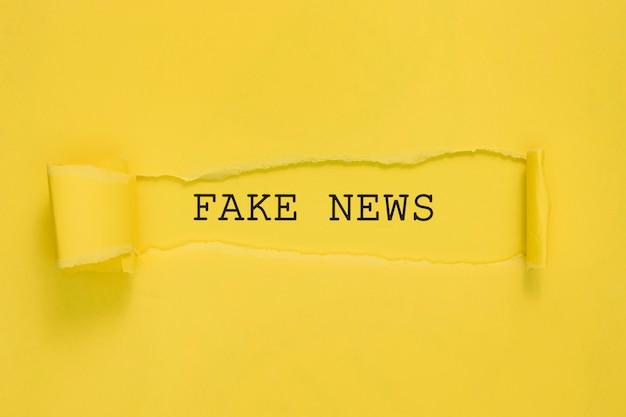 Papel de notícias falsas rasgado na parede amarela Foto gratuita