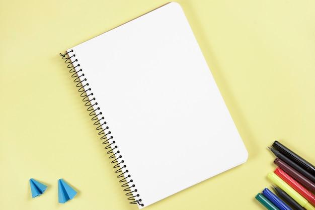 Papel de ofício dobrado e caneta de ponta de feltro, perto do bloco de notas de espiral em branco sobre fundo amarelo Foto gratuita