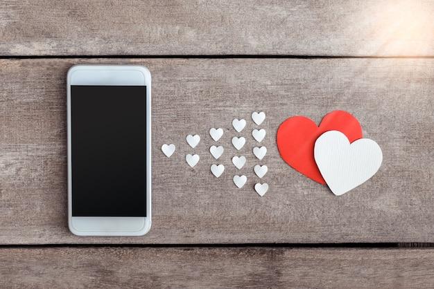 Papel de smartphone e corações em fundo de madeira Foto Premium