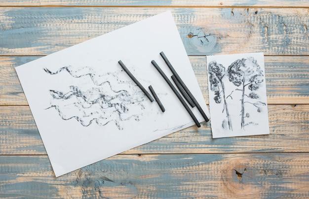 Papel e arte desenhados suprimentos vara de carvão na mesa de madeira Foto gratuita