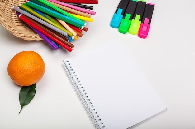 Papel e canetas de feltro coloridas na mesa branca Foto Premium