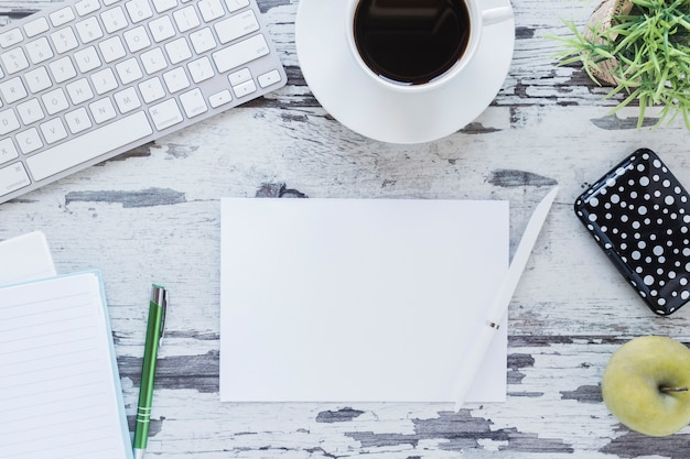 Papel e lápis perto da xícara de café e teclado Foto gratuita