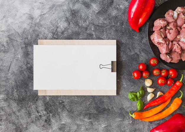 Papel em branco branco na prancheta com ingredientes para fazer carne no pano de fundo texturizado Foto gratuita