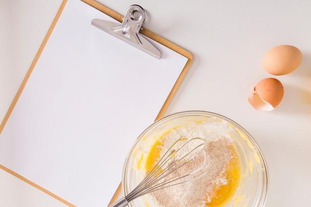 Papel em branco branco na prancheta com ovo e farinha tigela em pano de fundo branco Foto gratuita