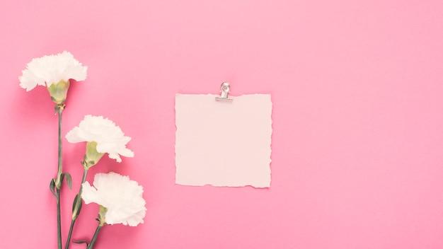 Papel em branco com flores brancas na mesa Foto gratuita