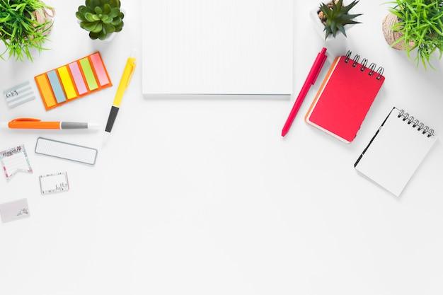 Papel em branco com material de escritório e vasos de plantas em pano de fundo branco Foto gratuita