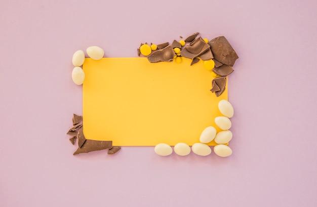 Papel em branco com pequenos doces e chocolate rachado Foto gratuita