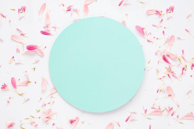 Papel em branco com pétalas de flores na mesa Foto gratuita