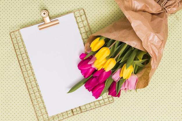 Papel em branco com prancheta e buquê de flores tulipa sobre fundo amarelo polka dot Foto gratuita