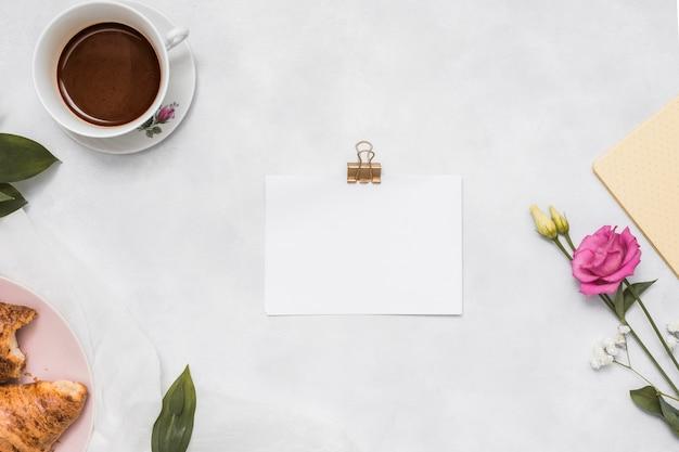 Papel em branco com rosa e copo de café Foto gratuita