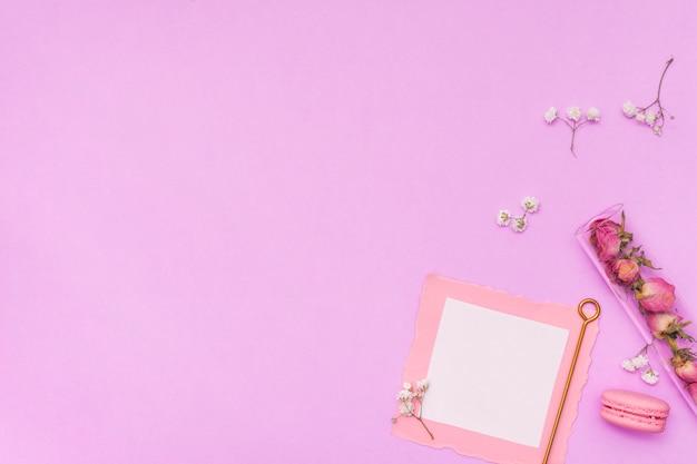 Papel em branco com rosas secas e macaroon Foto gratuita