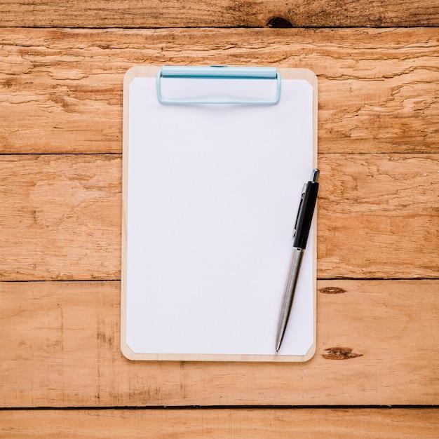 Papel em branco na prancheta com caneta esferográfica sobre a mesa de madeira Foto gratuita