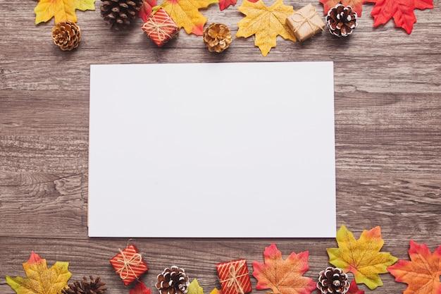 Papel em branco vista superior com folhas de bordo coloridas, cones, pequenas caixas de presente na superfície de madeira Foto Premium
