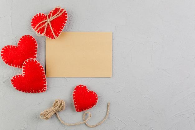 Papel marrom em branco entre corações de pelúcia Foto gratuita