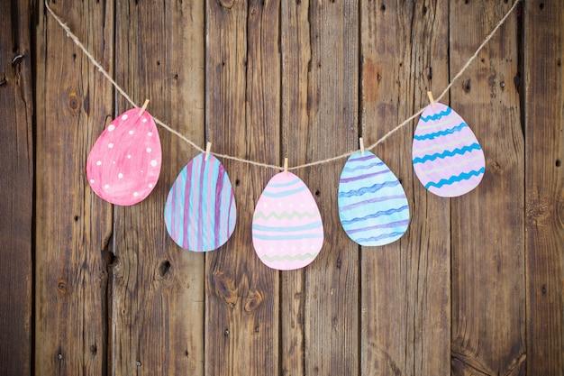 Papel páscoa pintada ovos pintados pendurar em prendedores de roupa no fundo Foto Premium