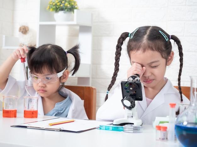 Papel pequeno da menina do irmão dois asiáticos que joga um cientista no laboratório de ciência com equipamento. aprendizagem e educação do garoto. Foto Premium