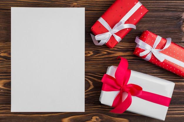 Papel perto de conjunto de caixas de presentes com fitas Foto gratuita