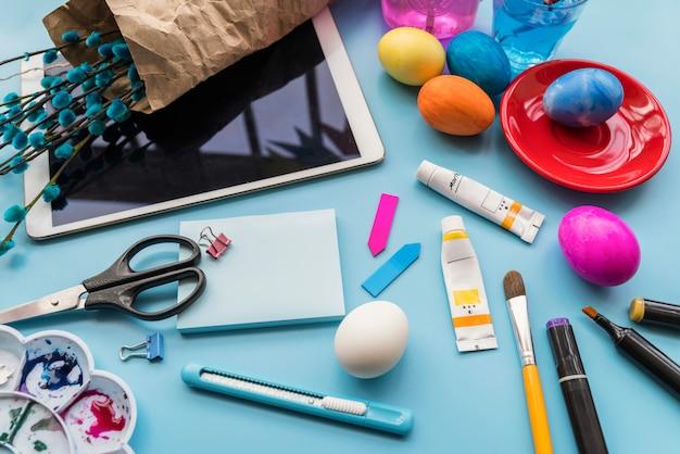 Papel perto de ovos de páscoa, galhos de salgueiro em tablet e artigos de papelaria Foto gratuita