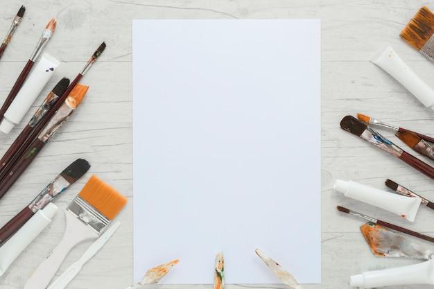 Papel perto de pincéis, tubos de tinta e facas Foto gratuita