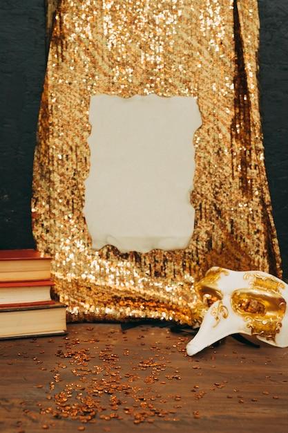 Papel queimado em tecido de lantejoulas douradas com máscara de carnaval na mesa de madeira Foto gratuita