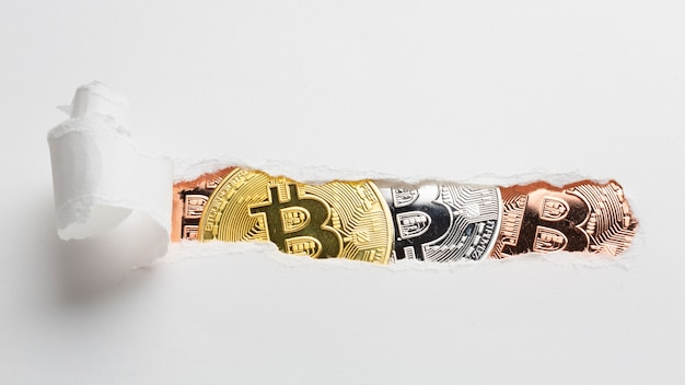 Papel rasgado revelando bitcoin Foto gratuita