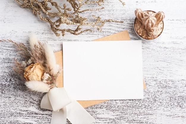 Papel vazio e envelope kraft com buquê de flores secas de cores neutras. suculenta dourada e decoração em mesa branca. espaço de trabalho moderno Foto Premium