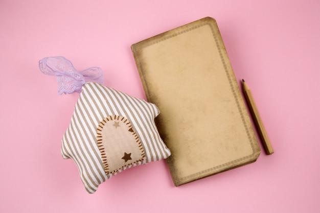 Papel velho vintage de vista superior, lápis e casa de brinquedo de pelúcia em um fundo rosa pastel Foto Premium