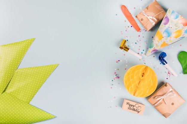 Papel verde triangular e itens de festa em fundo cinza Foto gratuita