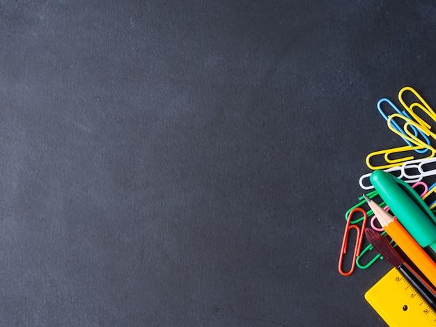 Papelaria colorida volta ao conceito de escola no fundo do quadro-negro Foto Premium