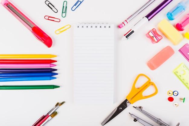 Papelaria da escola com o bloco de notas no centro Foto gratuita