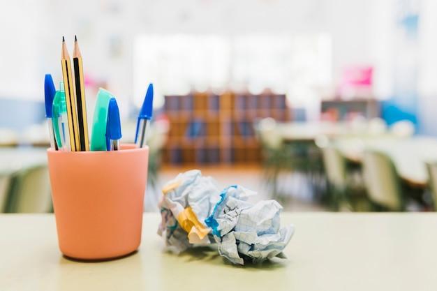 Papelaria da escola no copo na mesa Foto gratuita