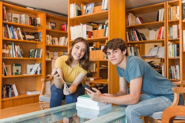 Par adolescente, com, dispositivos, em, biblioteca Foto gratuita