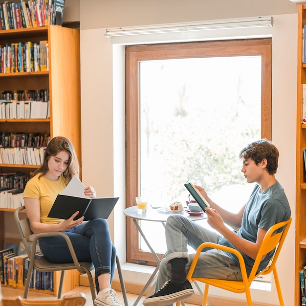 Par adolescente, leitura, em, biblioteca Foto gratuita