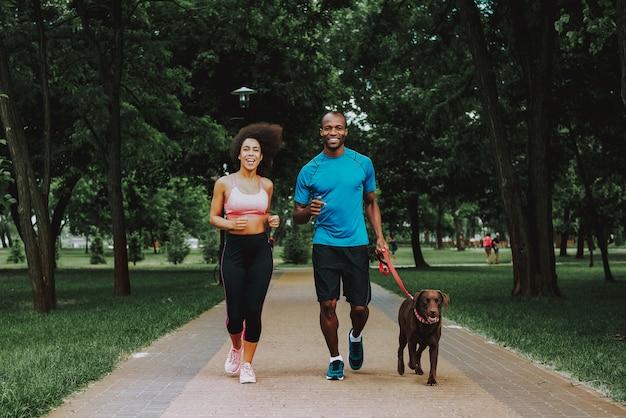 Par americano africano, em, sportswear, cachorro andando Foto Premium