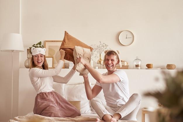 Par apaixonado rindo e brincando na cama. homem e mulher lutam almofadas. jovem casal feliz bate os travesseiros na cama em um quarto em casa Foto Premium