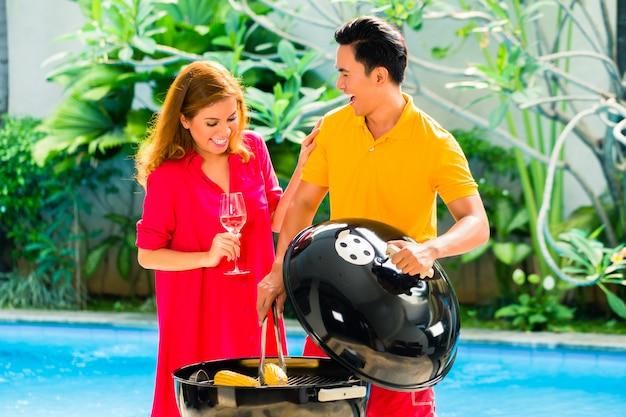 Par asiático, tendo, churrasco, em, a, piscina Foto Premium