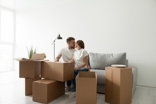Par, beijando, sentar sofá, em, sala de estar, com, caixas Foto gratuita