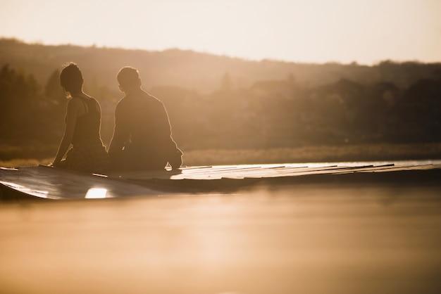 Par, cais, pôr do sol Foto gratuita