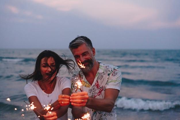 Par, celebrando, com, sparklers, praia Foto Premium