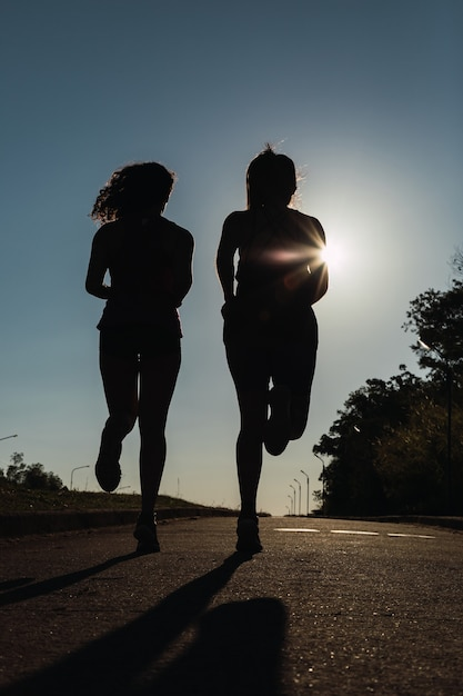 Par de amigos correndo ao pôr do sol com uma silhueta Foto Premium