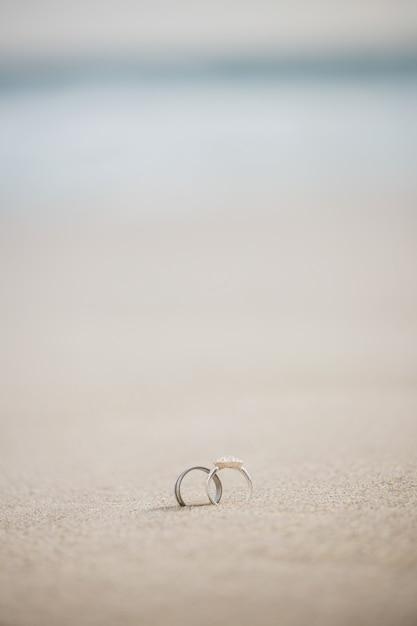 Par de anel de casamento na areia Foto gratuita