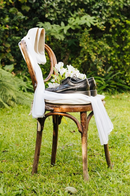Par de casamento sapatos de salto altos e sapatos com cachecol e buquê de flores na grama verde no parque Foto gratuita