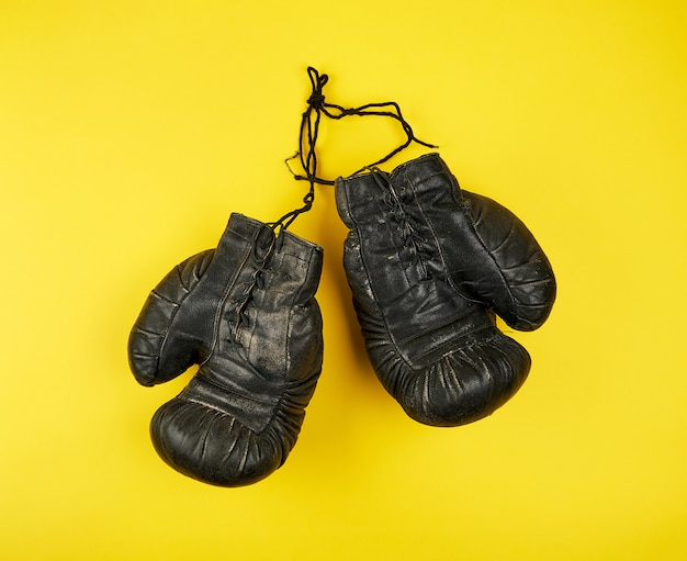 Par de couro preto muito velhas luvas de boxe em um fundo amarelo Foto Premium