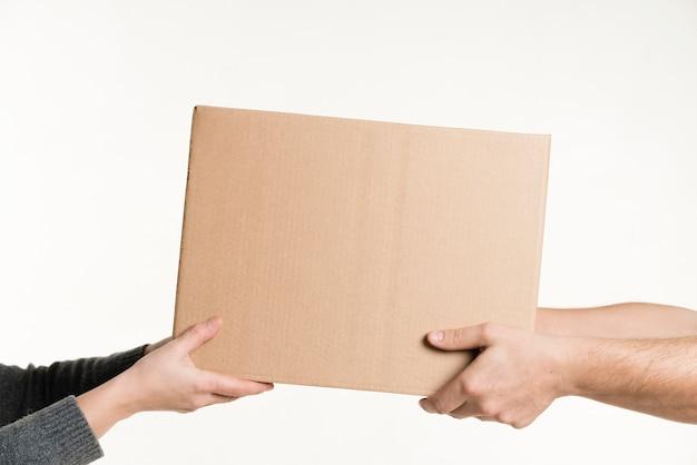Par de mãos segurando uma vista frontal de papelão Foto gratuita