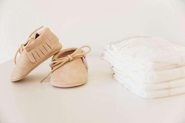 Par de sapatos de bebê e empilhados de fralda em fundo bege Foto gratuita