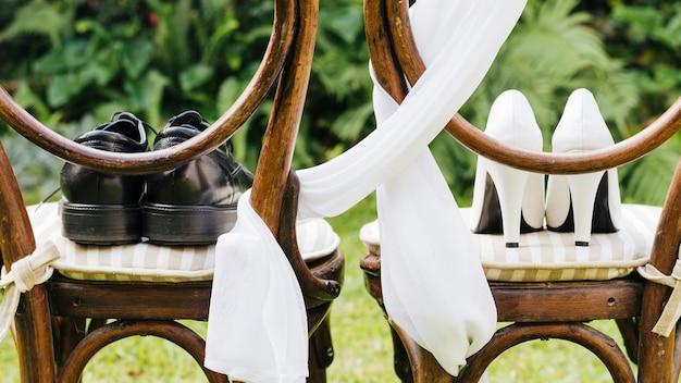Par de sapatos de casamento na cadeira de madeira no parque Foto gratuita
