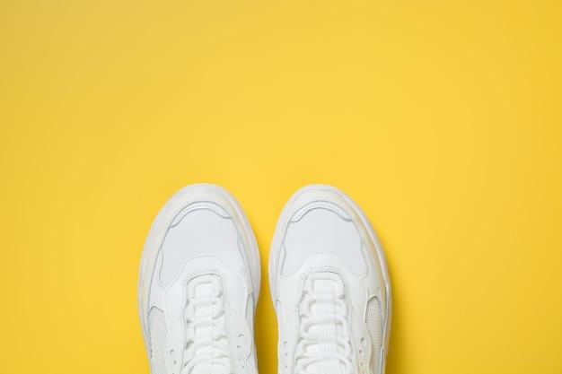Par de tênis femininos brancos em amarelo. flat lay, top view minimal. Foto Premium